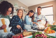 Four friends at sunlit kitchen royalty free stock image