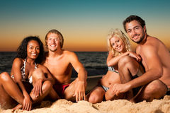 Four friends at sunset beach Royalty Free Stock Photos