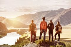 Four friends sunset mountains travel concept. Four friends stands on view point and looking at sunset mountains and river. Adventures travel concept with space stock image