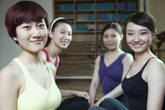 Four friends talking and smiling in a yoga studio Stock Photos