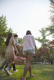 Four friends walking into a park to have a picnic on a spring day, carrying a picnic basket and a soccer ball Stock Photo