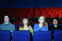 Four friends watch movie in cinema theater Royalty Free Stock Photos