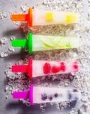 Four frozen fresh fruit popsicles on sticks. Four frozen fresh fruit popsicles with different natural flavors on bright colored plastic sticks, aligned on Stock Image