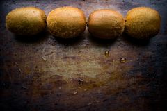 Four kiwi fruits are displayed in the top row on a worn dark background with an empty space. Four fruits of ripe kiwi are displayed in the top row on a worn stock photo