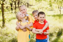 Four fun happy kids hugging outdoors royalty free stock photography