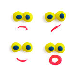 Four funny faces - eyes and mouths - made of multicolored plasticine with different expressions on the white background. Royalty Free Stock Photo