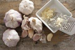 Four garlic bulbs beside shredded cloves Royalty Free Stock Photos