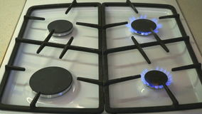 Four gas burners burn blue flame on a gas stove. They go out by turns stock video footage