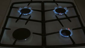 Four gas burners burn blue flame on a gas stove. They go out by turns stock video