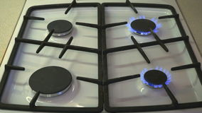Four gas burners burn blue flame on a gas stove. They light up in turn stock video footage