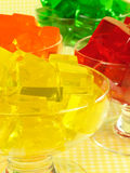 Four Gelatin Desserts. Glasses of orange, green, red, and yellow cubed gelatin stock images