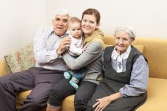 Four generation family sitting on sofa. At home Stock Photos