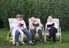 Four generations of men reading in the garden. On sunny day Royalty Free Stock Photography