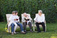 Four generations of men reading in the garden. On sunny day Royalty Free Stock Photo