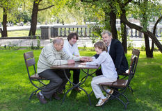 Four generations of men sitting at a wooden table in a park, laughing and talking Stock Images