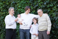 Four generations of men standing in the garden. Four generations of men standing in a park on sunny day Stock Image