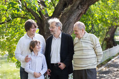 Four generations of men standing in a park looking at each other and laughing. On summer day Royalty Free Stock Photos