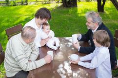 Four generations of one family sitting at a wooden table. In the garden drinking coffee and tea on summer day stock image