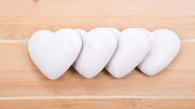 Four gingerbread hearts on wooden background. Four white gingerbread hearts on wooden background Royalty Free Stock Image