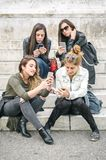 Four girl friends happy watching internet social media in smartp. Hone. Every one with his own phone Stock Image