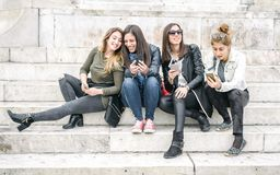 Four girl friends happy watching internet social media in smartp. Hone. Every one with his own phone Stock Photo
