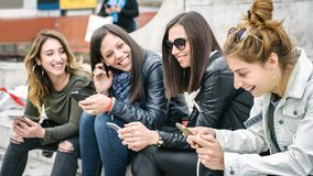 Four girl friends happy watching internet social media in smartp. Hone. Every one with his own phone Royalty Free Stock Photos