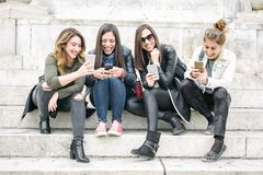 Four girl friends happy watching internet social media in smartp. Hone. Every one with his own phone Stock Photos