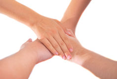 Four girl friends holding hands in a pile of unity and teamwork royalty free stock images