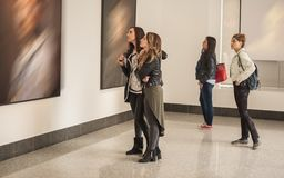 Four girl friends looking at modern painting in art gallery royalty free stock photography