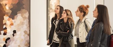 Four girl friends looking at modern painting in art gallery stock photography