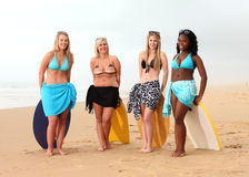 Four girl friends resting on surf boards. A roup of four girl friends are standing with their boogie boards or surf boards behind them, they are laughing and Stock Photo