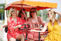 Four girl friends on a tourist bike Royalty Free Stock Photography