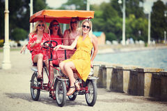Four girl friends on a tourist bike Royalty Free Stock Image
