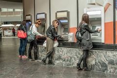 Four girl friends withdrawing money from credit card at ATM. Business woman stock photos