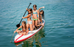 Four girlfriends having fun on stand up board during summer beac Stock Images