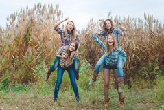 Four girlfriends playing horses and having fun in Royalty Free Stock Images