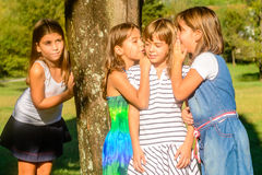 Four Girlfriends playing in the park. Four little girls playing and whispering in the park stock photography
