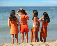 Four girls on the beach. Four girls in orange clothes standing on the beach Stock Image