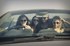Four girls in a car going on vacation Stock Image