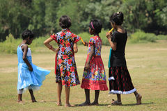Four girls with colorful dresses. Four girls standing in the field with colorful dresses. During festival they weared colorful dress. They are chatting together stock image