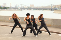 Four girls dancing on embankment Stock Image