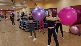 Four girls doing sports with fitness balls in gym.