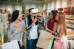 Four girls are having some fun. Brunette in shirt has VR glasses on her face and keeping her hands in the air while her. Friends are laughing and smiling Stock Image