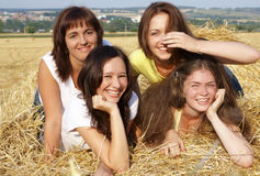 Four girls on hayloft. In summer day stock image