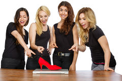 Four girls with laptop and red shoe Stock Images