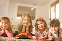 Four girls lying on the floor. Four girls lying on the floor and and doing their homework. Looking at camera. Portrait Royalty Free Stock Photography