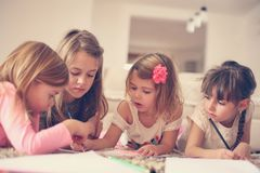 Four girls lying on the floor. Four girls lying on the floor and write their homework. Close up Stock Photos