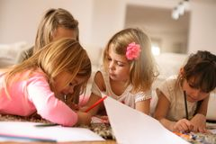 Four girls lying on the floor. Four girls lying on the floor and write their homework.Close up image Royalty Free Stock Photo