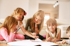 Four girls lying on the floor. Four girls lying on the floor and write their homework. Close up image Stock Photo