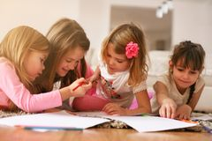 Four girls lying on the floor. Four girls lying on the floor and write their homework. Close up image Royalty Free Stock Photos